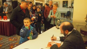 Signing line, with Maureen in the background